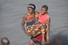 A lady is lifted from a boat to the shore, at the Ferry docking terminal in Freetown